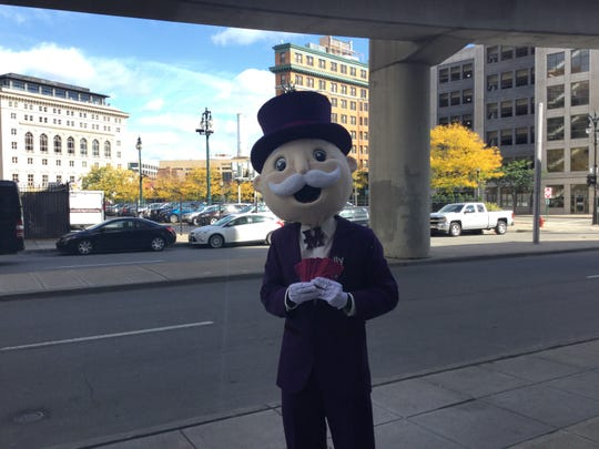 "Mr. Monopoly hands out ""money"" to pedestrians outside of the Detroit Opera House Thursday, Oct. 17, 2019."