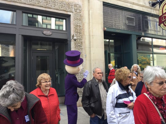 Mr. Monopoly waves to a group of seniors boarding a bus outside of  Detroit Beer Company Thursday, Oct. 17, 2019.