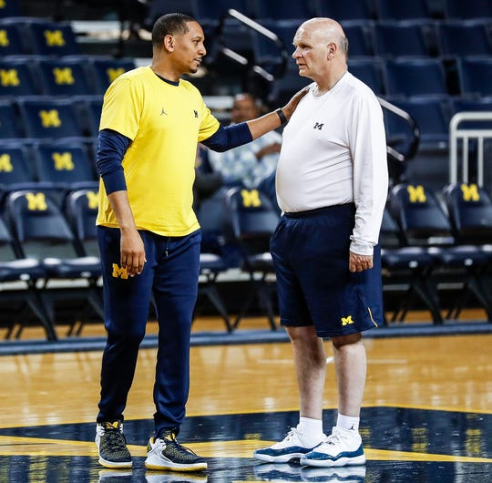 Michigan assistant coach Howard Eisley talks to  associate head coach Phil Martelli at practice during media day at Crisler Center in Ann Arbor, Thursday, Oct. 17, 2019.