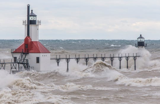 Large waves, on Lake Michigan, caused by high winds, crash into the Saint Joseph Lighthouse and pier on Wednesday, Oct. 16, 2019, in Saint Joseph, Mich.