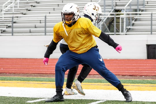North Farmington's Sylvon Brown, center, practices with teammate Dominic Mathis-Nelson at North Farmington High School in Farmington Hills, Wednesday, Oct. 16, 2019.