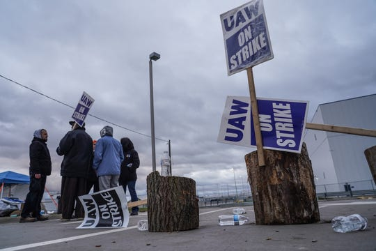 UAW strike signs are placed on stumps as UAW members stand on strike outside of General Motors Flint Assembly on Wednesday, October 16, 2019.