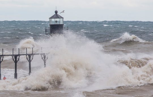 Large waves on Lake Michigan, caused by high winds, crash into the Saint Joseph Lighthouse and pier on Wednesday, Oct. 16, 2019, in Saint Joseph.