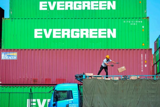 In this Monday, Oct. 14, 2019, photo, a worker loads imported goods on a truck at a distribution company outside the container port in Qingdao in east China's Shandong province.