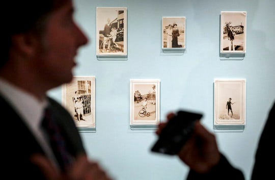 Declan Kiely, director of special collections and exhibitions at the New York Public Library, gives an interview next to childhood photographs of author J.D. Salinger.