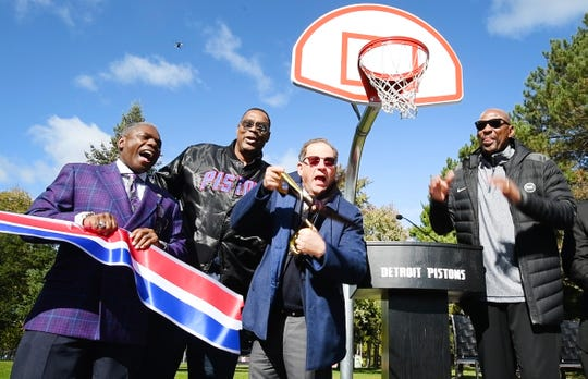 Detroit City Council member Roy McCalister Jr., left; NBA champion Rick Mahorn; Pistons Vice Chairman Arn Tellem; and two-time NBA champion Earl Cureton cut the ribbon Thursday on the refurbished basketball court in Palmer Park, one of 17 courts refurbished by the Detroit Pistons in Detroit.