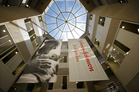 In this July 30, 2013, file photo, large banners hang in an atrium at the headquarters of Johnson & Johnson in New Brunswick, N.J.  Johnson & Johnson has agreed to a $117 million multistate settlement over allegations it deceptively marketed its pelvic mesh products, which support women's sagging pelvic organs.