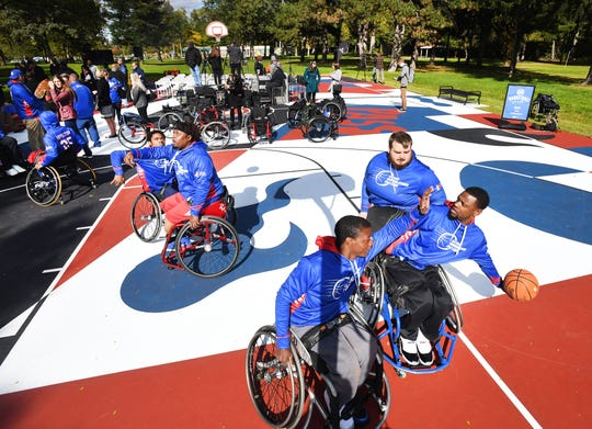 Detroit Wheelchair Pistons players Clayton Buchanan puts up a shot against some tough defense from Robert Wells and Alex Asleh on the newest  basketball court refurbished by the Detroit Pistons, in Palmer Park, one of 17 throughout Detroit.