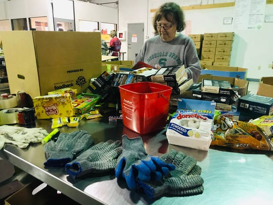 Sandy Karnes of Okemos volunteers at the Greater Lansing Food Bank on Thursday, Oct. 17, 2019, the same day state officials visited the food bank to announce increases in asset limits for food and cash assistance.