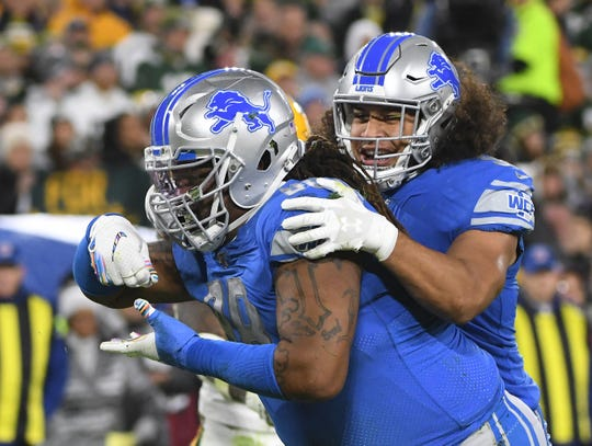 Lions rookie linebacker Jahlani Tavai, right, played 44 snaps against the Packers on Monday night.