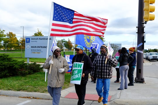 Karlton Byas, center, marches with other UAW members Thursday outside the Detroit-Hamtramck Assembly Plant, where he does health and safety training for the UAW. He said they are hopeful and optimistic that the tentative agreement will bring an end to their strike.