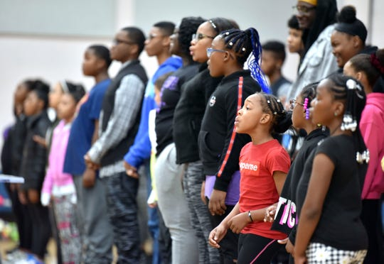 Briana Hammond, third from right, 8, of Detroit, sings during practice.
