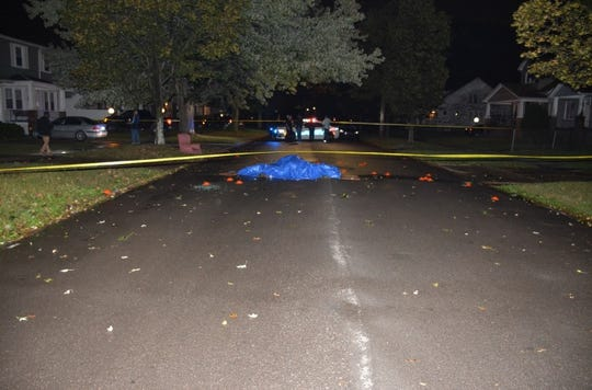 A blue tarp covers the body of a Latin Counts gang member outside a home in the 2400 block of South Liddesdale Street in October 2017. Orange evidence markers show where investigators found bullet casings.