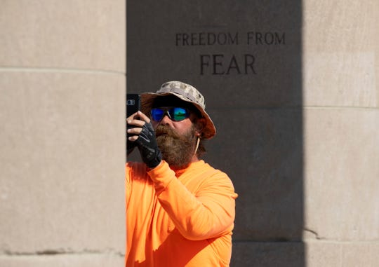 Van Booth, a retired U.S. Army staff sergeant, makes a picture of one of the pillars of the Four Freedoms Monument in Evansville Thursday afternoon. The veteran is traveling to Myrtle Beach, S.C. on foot after beginning his cross country walk in San Juan Capistrano, Calif., in February. Walking for Life is meant to raise awareness of Operation Song, an organization that helps veterans through the use of song.