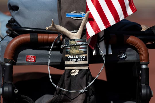 Van Booth, a retired U.S. Army staff sergeant, adorns his push cart with memorabilia from his trek across America... Walking for Life. An American flag; a deer antler from Nevada; and even a teddy bear he found along Indiana State Road 62 Wednesday morning, all have found a spot.