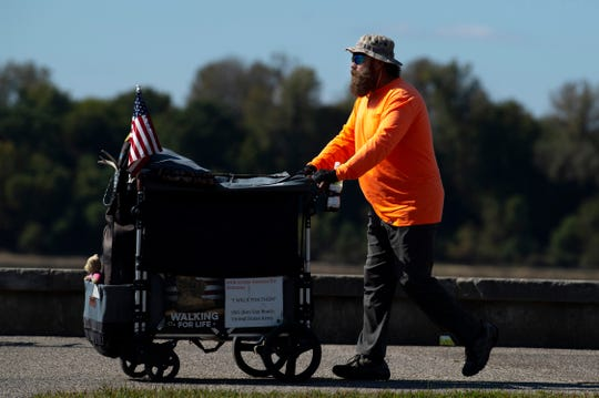 Van Booth, a retired U.S. Army staff sergeant, continues his trek across America – Walking for Life – near Dress Plaza in Downtown Evansville Thursday afternoon. The veteran started his walk in San Juan Capistrano, Calif., last February and will finish in Myrtle Beach, S.C.