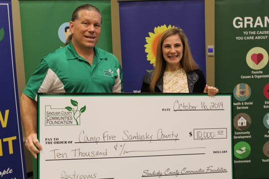 Tom Bowlus, pictured left, gives a grant check of $10,000 to Jennifer Rupp of Camp Fire Sandusky County Wednesday at the Sandusky County Communities Foundation's 2019 grant award program. The foundation awarded approximately $72,000 in grants to 15 Sandusky County organizations and municipalities.
