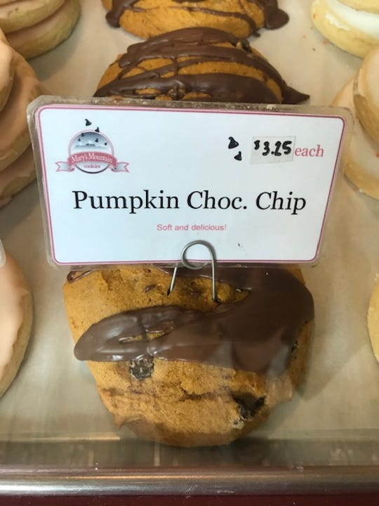 Pumpkin chocolate chip cookies rest behind display glass inside Old Town's Mary's Mountain Cookies location.