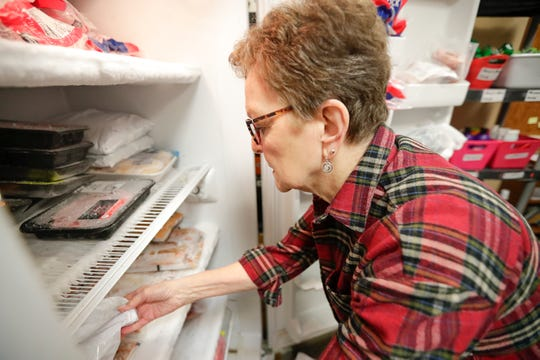 Volunteer Judy Bohne takes meat out of the freezer on Thursday at the Salvation Army of Greater Green Bay food pantry.