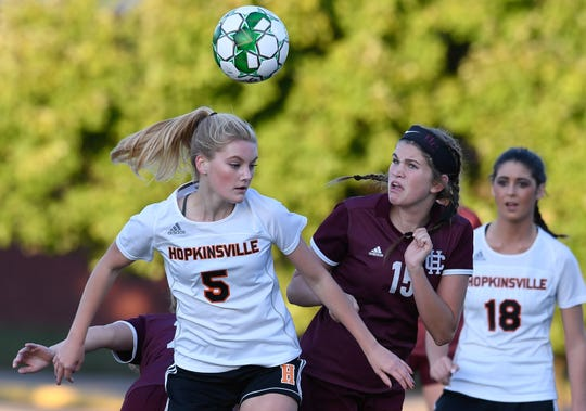 Hopkinsville's Grasen Givens (5) and Henderson County's Preston Hazelwood (15) try to control the ball as the Henderson County Lady Colonels play the Hopkinsville Lady Tigers in the second round of the girls' regional soccer tournament at Hopkinsville's Stadium of Champions Wednesday evening, October 16, 2019.