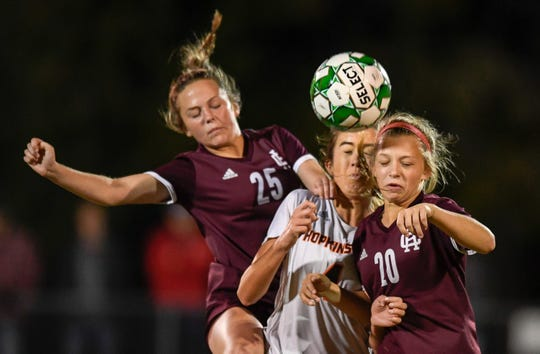 Henderson County's Kate Reusch (25) and Morgan Green (20) battle Hopkinsville's Sarah Johnston (4) as the Henderson County Lady Colonels play the Hopkinsville Lady Tigers in the second round of the girls' regional soccer tournament at Hopkinsville's Stadium of Champions Wednesday evening, October 16, 2019.