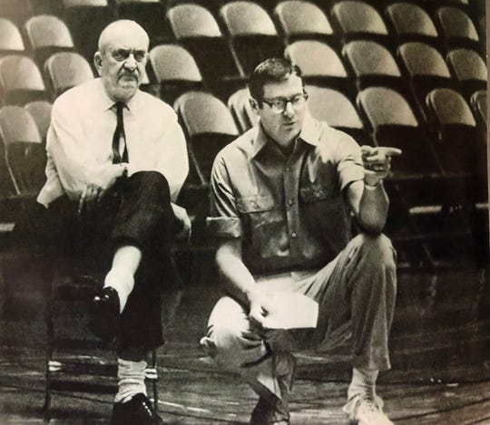 Legendary Kentucky basketball coach Adolph Rupp scowls while his young assistant (and eventual successor) makes a point during a team practice in the 1960s.