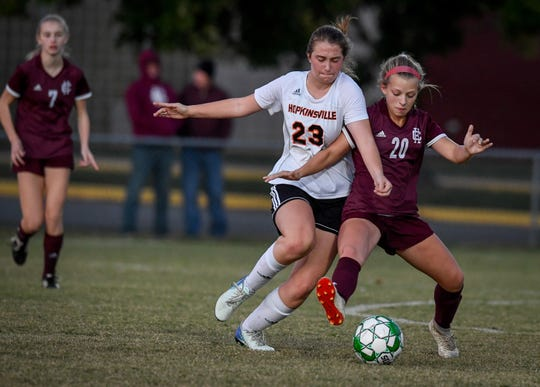 Hopkinsville's Abby Moss (23) and Henderson County's Morgan Green (20) fight for the ball as the Henderson County Lady Colonels play the Hopkinsville Lady Tigers in the second round of the girls' regional soccer tournament at Hopkinsville's Stadium of Champions Wednesday evening, October 16, 2019.