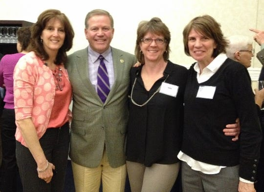 Notre Dame football coach Brian Kelly posed in 2014 with three of his softball players from Assumption College's 1983 team. From left are  left fielder Tricia (Carter) Poirier, pitcher Kate Hubbard and third baseman Helen Russell. Assumption College is in Worcester, Mass.
