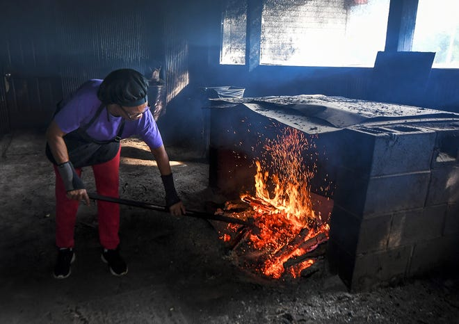 Helen Turner, owner of Helen's BBQ in Brownsville, Tenn., kindles a fire inside the smokehouse in the back of her restaurant. The fire is started on one side of the smokehouse and is transferred to the smoker where the meats are prepared.