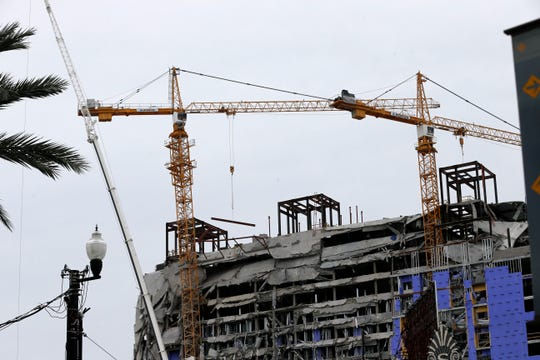 Two unstable cranes loom over the New Orleans Hard Rock Hotel, which collapsed last Saturday, killing three workers. Authorities say explosives will be strategically placed on the cranes in hopes of bringing them down with a series of small, controlled blasts ahead of approaching tropical weather.