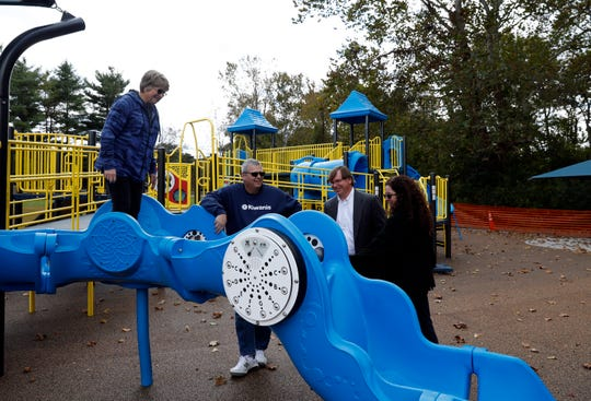 Joan Miller, left, stands on a walking slide as she and Craig Miller, second from left, Mike Tharp Jr., third from right, and Fran Tiburzio explore the new all access playground at Hunter Park in Lancaster. The playground, which was built with more than $300,000 in donations from the Kiwanis Club of Lancaster, will open the public Oct. 29.