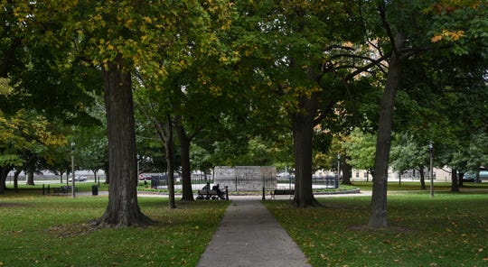 Two men sit on a park bench at Reutter Park in downtown Lansing, pictured Thursday, Oct. 17, 2019.
