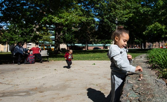 """""""We always walk through the park on our way to the library,"""" Shawnee Gonzalez, left, said Monday, Oct. 2, 2019, as she and  boyfriend Daryl Smith, Jr., left, watch her daughter La'Reyna, 4, and brother Kemen, 2, at Reutter Park in downtown Lansing, Monday, Oct. 7, 2019."""