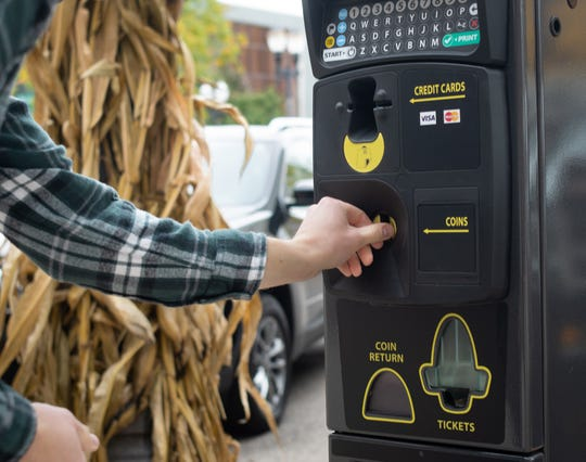 Justin Pauken, right, of Detroit uses one of downtown Lansing's new parking pay stations Thursday morning, Oct. 17, 2019.  Drivers can now pay via smartphones through the Passport Parking app, with a debit or credit card, or with coins.  Nearly 3,000 parking spaces throughout the city will utilize the new technology.