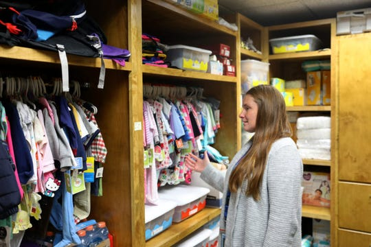 Kari Kerber points to donated clothes and other items in a closet at the Chippewa County Human Services in Chippewa Falls that will be distributed to drug-endangered children. The county has been hit hard by an increase in methamphetamine use.