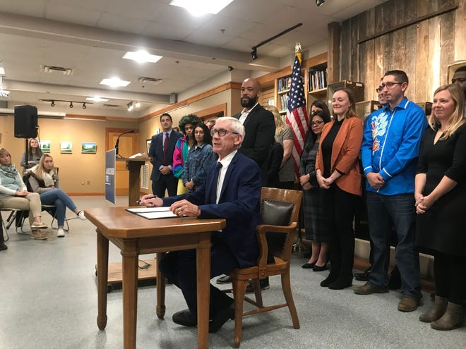 Gov. Tony Evers, seated, prepares to sign an executive order establishing a task force on climate change during an appearance at the Urban Ecology Center in Riverside Park.