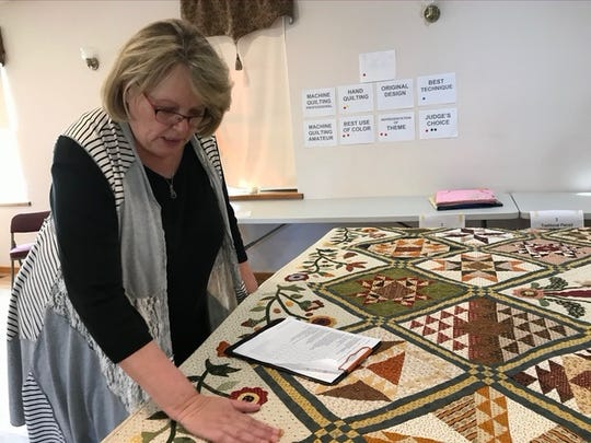 Kathi Eubank of Hot Springs Village evaluates quilts made by Hill 'N Hollow Quilters Guild members. Eubank was certified to judge quilt shows by the National Association of Certified Quilt Judges. This quilt and others will be displayed at the 2019 Autumn in the Ozarks quilt show, which will be held Thursday-Saturday, Oct. 17-19, at the Baxter County Fairgrounds Educational Building in Mountain Home. In addition to more than 250 quilts, the show will feature unique gifts and quilting supplies offered by vendors and guild members, lunch and snacks provided by the Patchwork Extension Homemakers Club, a quilt drawing and a live auction of decorated boxer shorts benefitting Peitz Cancer Support House. For more information, contact Vicki Kauth at (870) 421-5369.