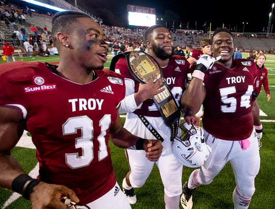 Troy linebacker A.J. Smiley (31), offensive lineman Kirk Kelley (78) and offensive lineman Tristan Crowder (54) celebrate with the belt after defeating South Alabama at Veterans Memorial Stadium on the Troy campus campus in Troy, Ala., on Wednesday October 16, 2019.