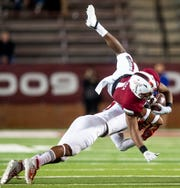 Troy wide receiver Kaylon Geiger (1) is upended by South Alabama linebacker A.J. DeShazor (3) at Veterans Memorial Stadium on the Troy campus campus in Troy, Ala., on Wednesday October 16, 2019.