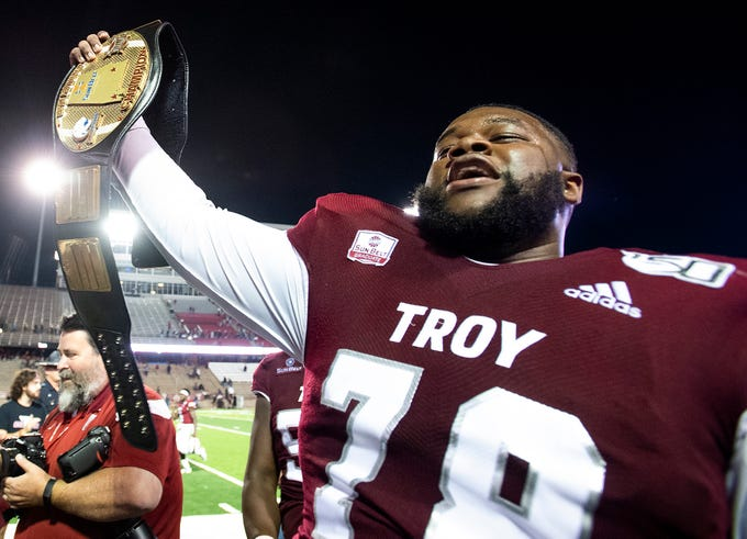 Troy offensive lineman Kirk Kelley (78) holds the championship belt after defeating South Alabama at Veterans Memorial Stadium on the Troy campus campus in Troy, Ala., on Wednesday October 16, 2019.