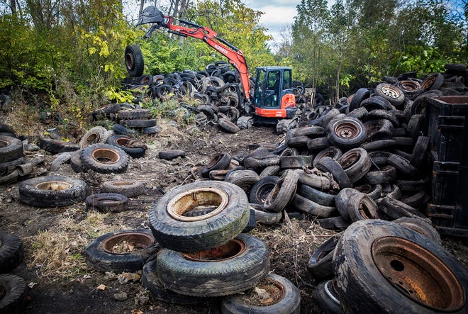 Contractors with Enviro Tire Recycling clean up a former tire dump site behind the Fresh Thyme grocery store on McGalliard Road. An estimated 41,000 tires were left at the site.