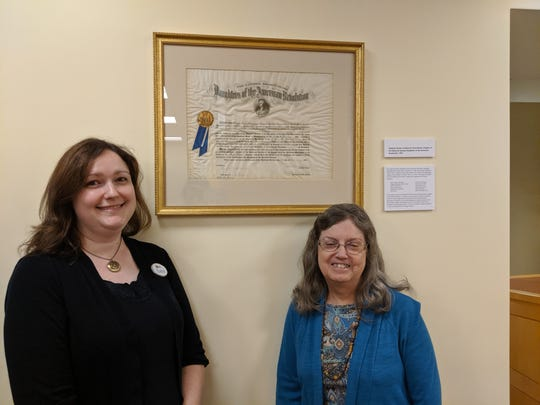 Librarian Sara McKinley and DAR Paul Revered Chapter Regent Diana Finney are pictured with the chapter's historic 1897 Charter.