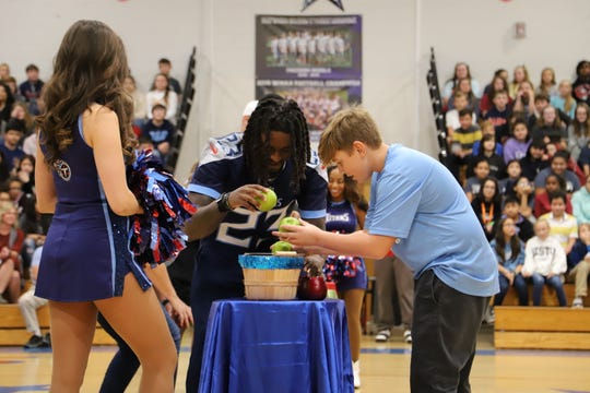 Tennessee Titans player Tye Smith plays a game with Caden Bergsrud at Freedom Middle School to promote healthy eating on Tuesday.