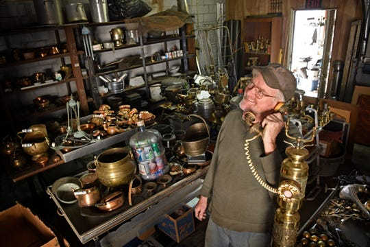 "Tom Davis of PocketMoney Recycling plays around with a fancy brass phone Thursday, Oct. 17, 2019. Davis is planning to have a yard sale and dispose of his ""trashy treasures"" that he has collected over the years."