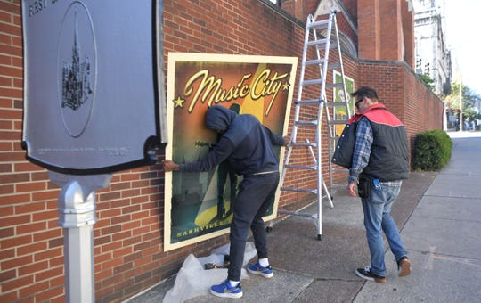 Big Visual Group workers Bobby Dowell and Lane Hirschfeld install five of Joel Anderson's Spirit of Nashville prints on the exterior wall at  Nashville First Baptist Church on Broadway on Thursday, Oct. 16, 2019.