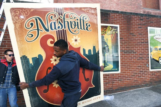 Big Visual Group workers Lane Hirschfeld and Bobby Dowell install five of Joel Anderson's Spirit of Nashville prints on the exterior wall at  Nashville First Baptist Church on Broadway on Thursday, Oct. 16, 2019.