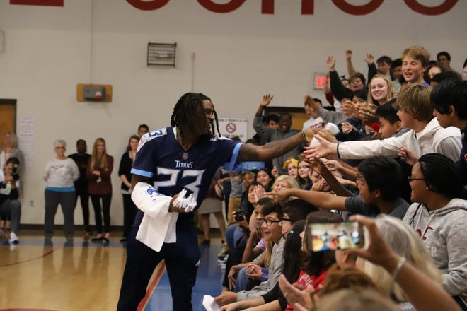 Tennessee Titans football player Tye Smith hands out T-shirts to students at Freedom Middle School.