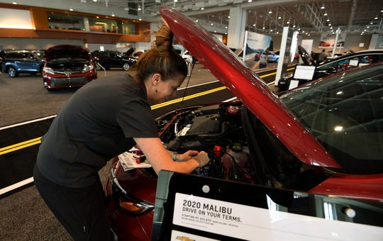 Jamie Makowski sets up a car for the Nashville International Auto Show at Music City Center Thursday, Oct. 17, 2019 in Nashville, Tenn.