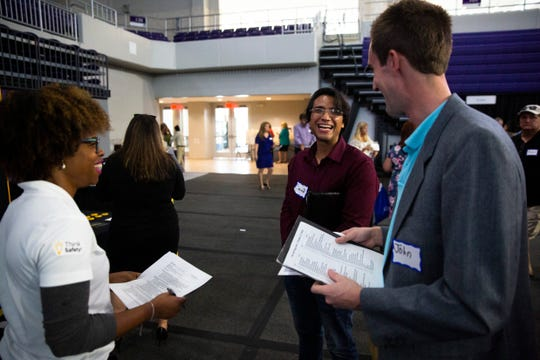 Treneice Collins, left, the campus recruiter for the Herc Rentals, talks to job seekers, David Duarte, center, and John Liebenguth, right, during a job fair at the Suncoast Credit Union Arena on Thursday, October 17, 2019, in Fort Myers.