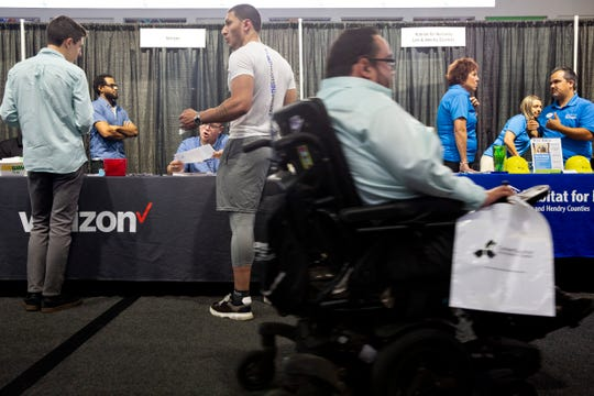 Rocky Castro drives his wheelchair past booths during a job fair at the Suncoast Credit Union Arena on Thursday, Oct. 17, 2019, in Fort Myers.